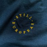 the words 'still european' are embroidered in golden yellow on a navy fabric background