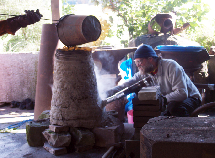 A white man with a beard leans into a cone-shaped furnace made of horse manure. A bucket held by a person out of shot tips something into the top of the cone.