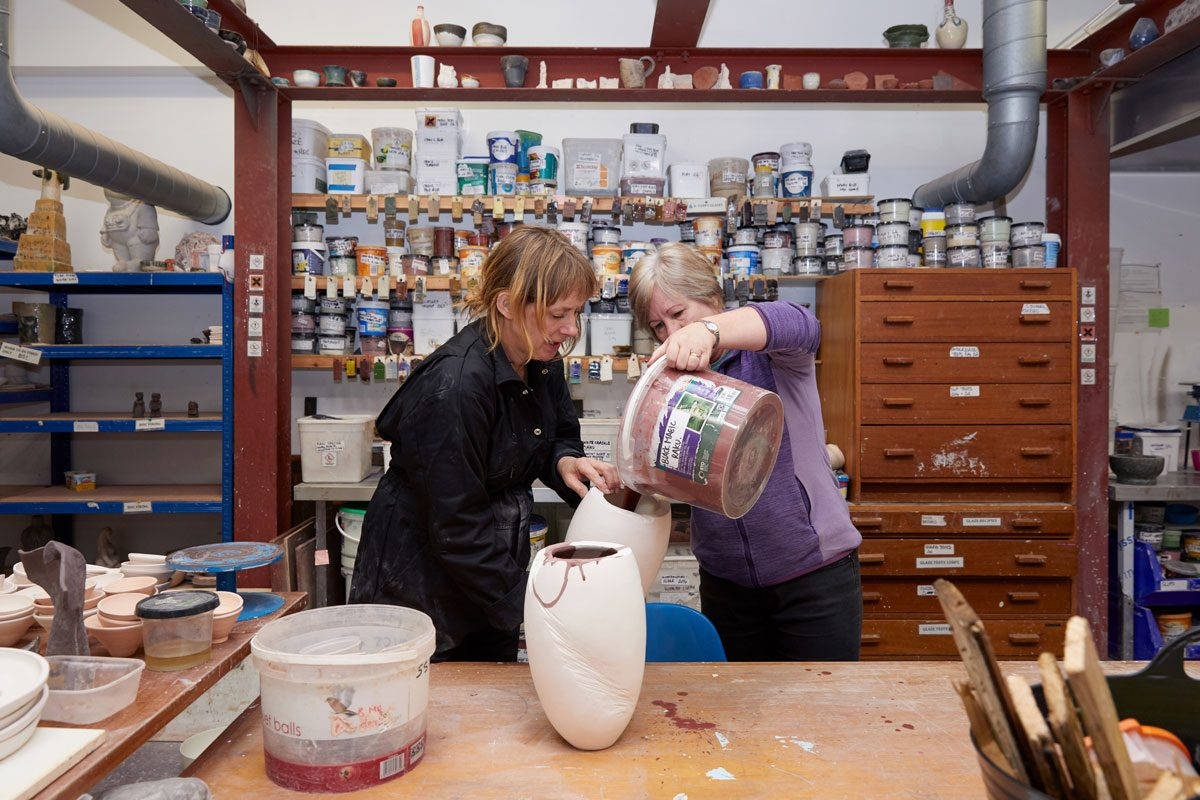 Two people juggle a large ceramic vessel in SSW's Ceramics workshop. One holds the white, bisque-fired vessel and the other pours a brown coloured glaze - from a large tub - into the vessel.