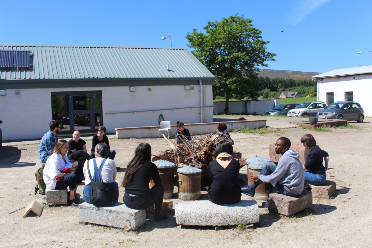 A group of people sit talking around the SSW firepit under blue skies