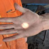 A dot of light is caught on the palm of an open hand