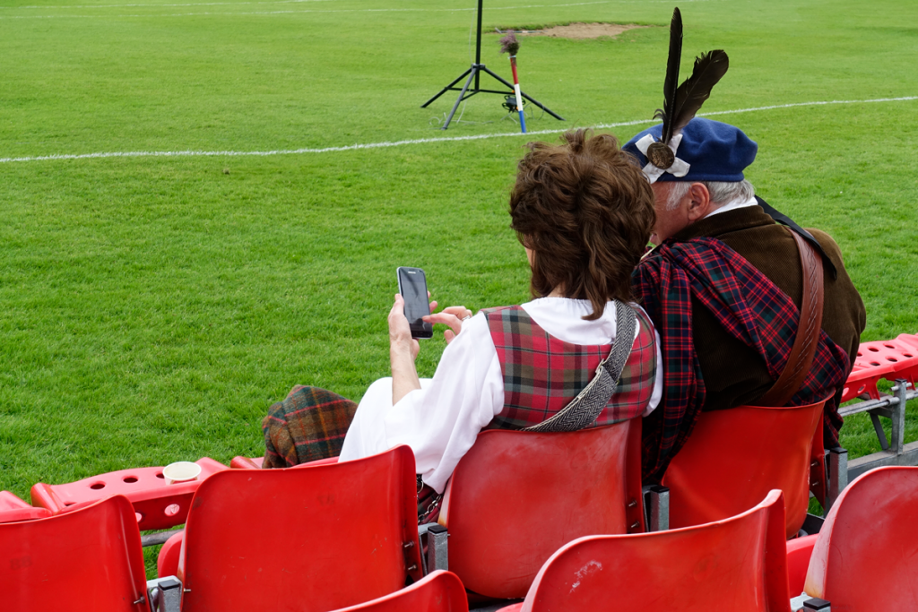 Two people in tartan look at a phone