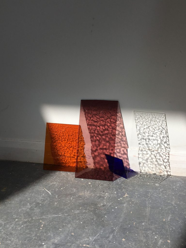 Textured and coloured glass leans against a wall with light creating interesting shadows