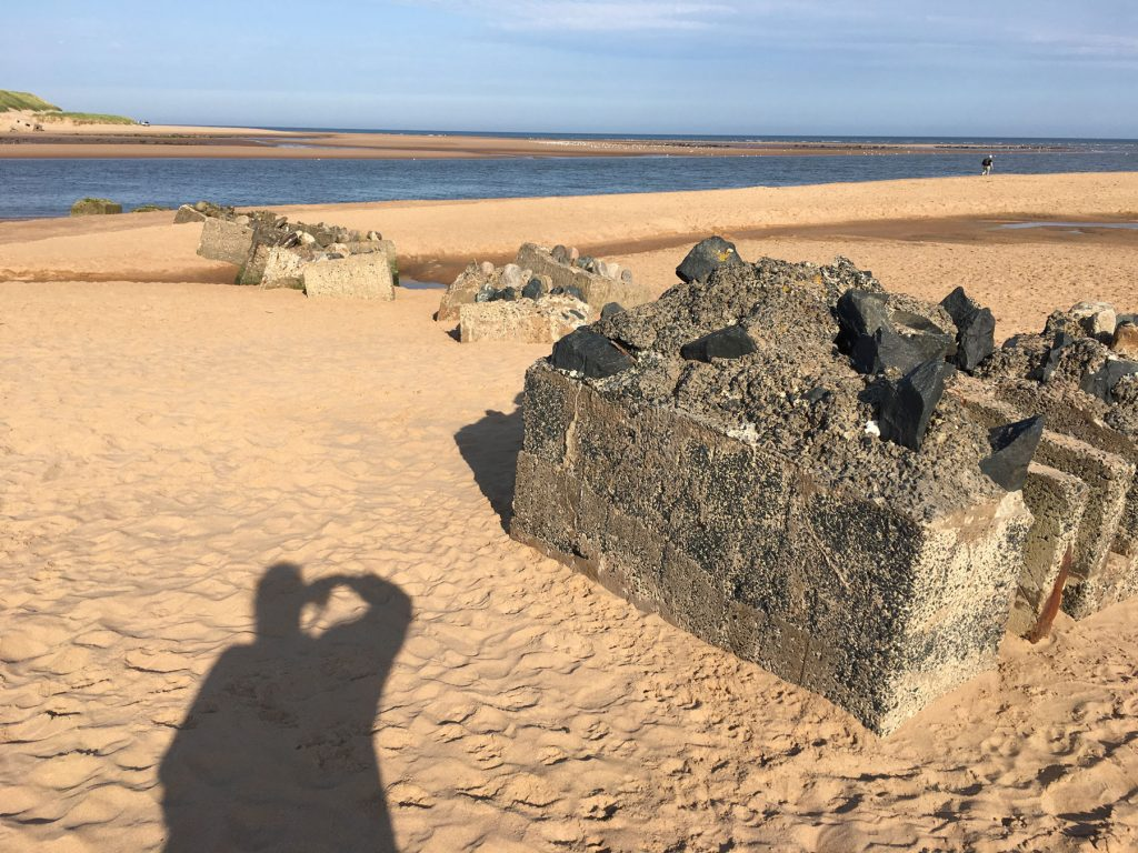 concrete defence bocks in a sandy beach leading to blue water and skies in the distance. The photographer's shadow stretches out on the sand.