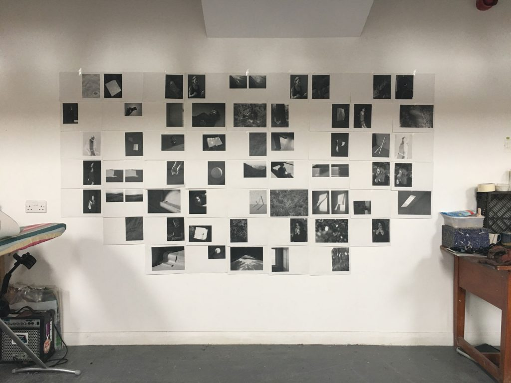 black and white photocopies of photographs laid out on a wall between a desk and an ironing board
