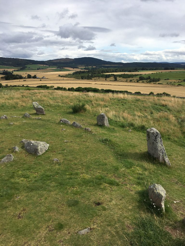 a standing stone circle with the landscape rolling out in the background