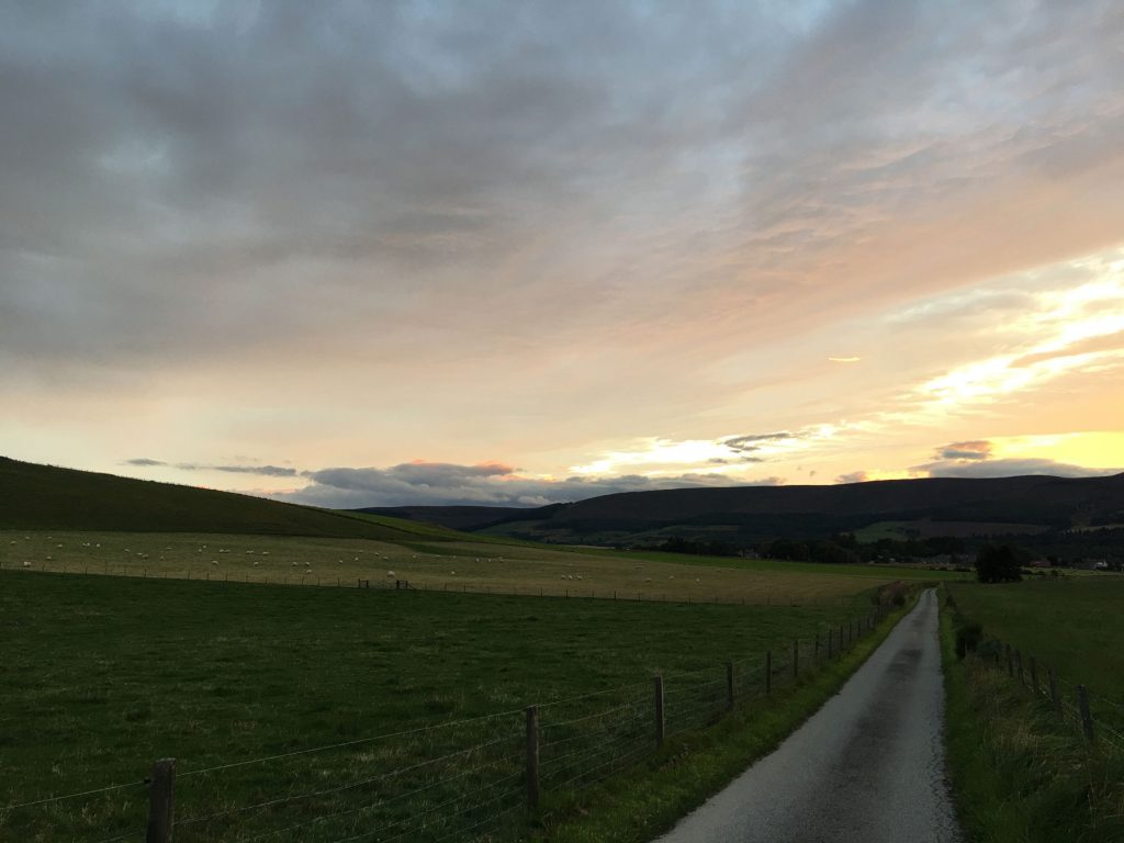 a golden sunset behind hills with a road stretching into the distance