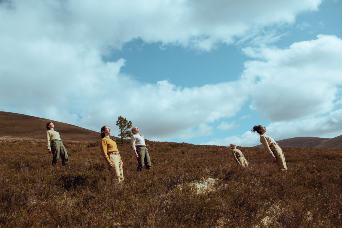 five dancers lean to look at the sky on a heather covered hillside