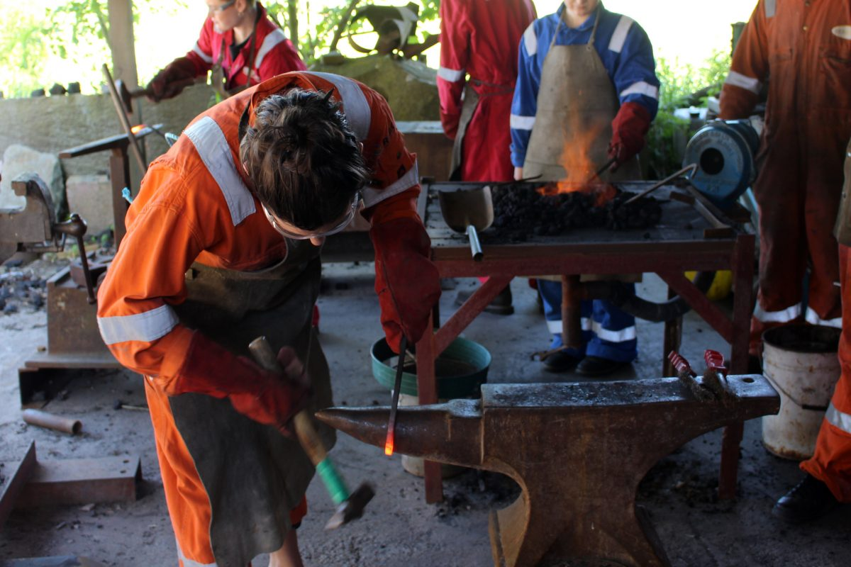 Someone hammers red hot steel bar on an anvil wearing an orange boiler suit