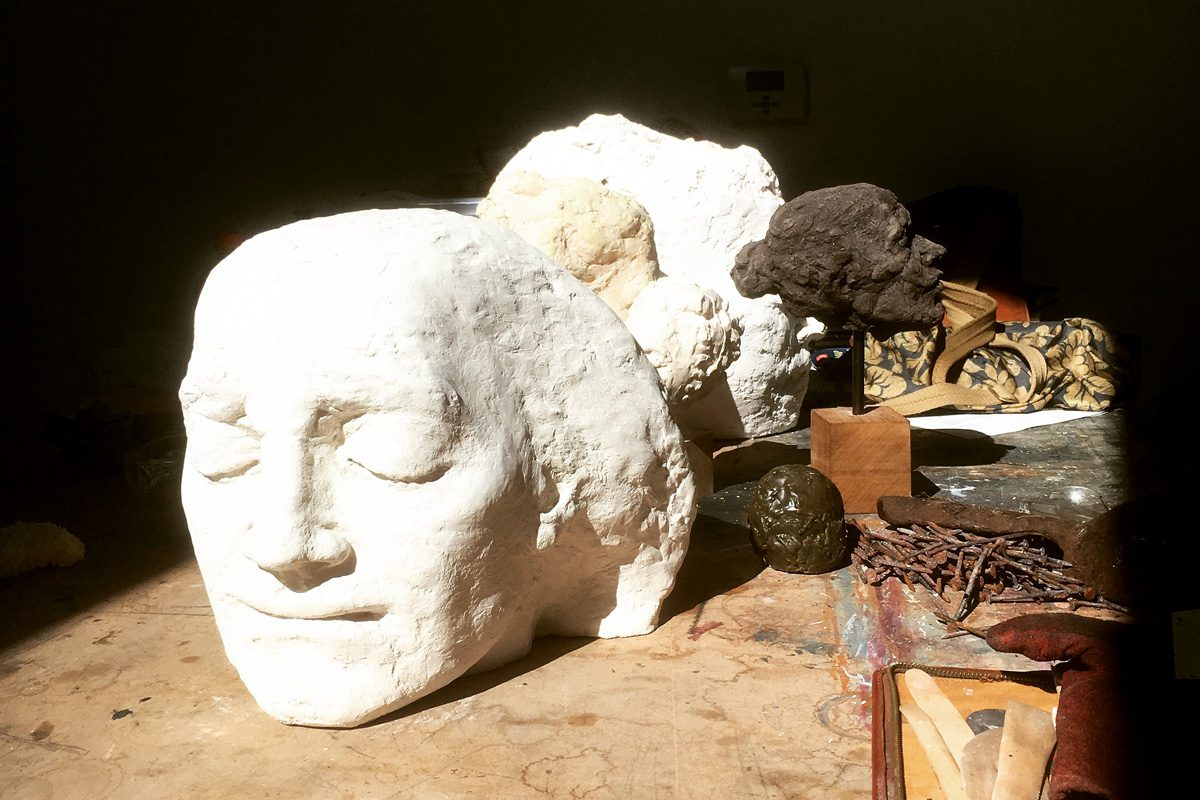 A plaster head bathes in sunlight with tools surrounding it.