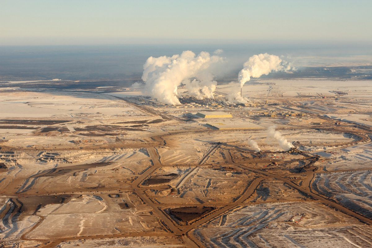 Smoke rises above the tar sands