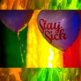 A heart shaped helium balloon with the words 'stay sick' on a brightly coloured and lit background