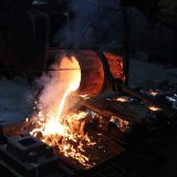 Glowing molten bronze pours out of a crucible into tin-foil covered sand moulds. The metal steams and splashes.