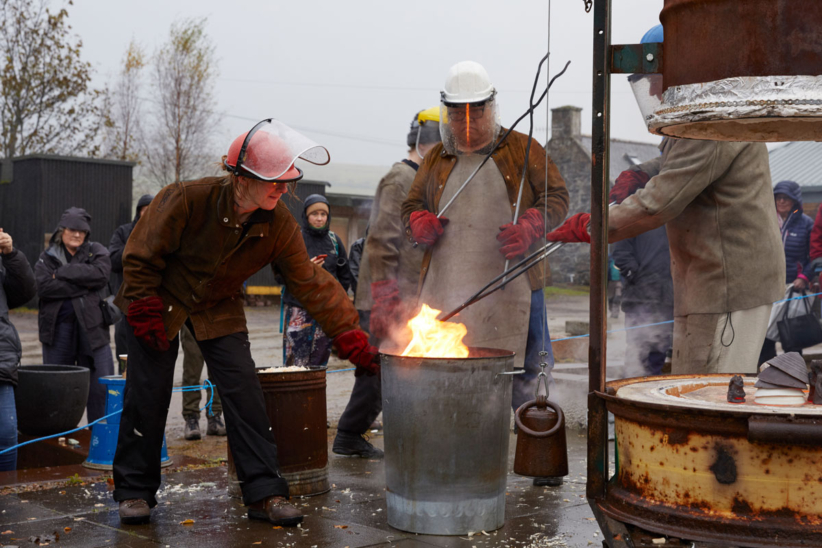 Three people wearing leather jackets and aprons, visors and gloves, lower ceramics into a flaming bin behind a glowing orange raku kiln. A crowd are watching.