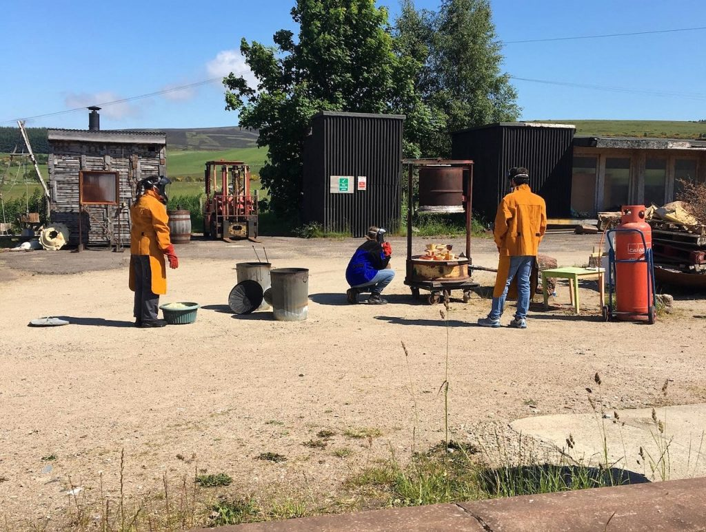 From a distance, Beth the ceramics technician wearing a deep cobalt leather jacket and visor crouches to look at the open contents of the raku kiln. Two other people wearing orange leathers and visors stand nearby. Raku kit such as metal dustbins and a large canister of propane are dotted around. They are in the SSW yard and it is gloriously sunny.