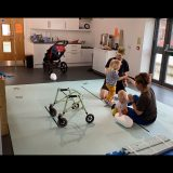 Laura and Murray sit on light blue foam mats on the floor and hold Rowan and Jude's hands. Rowan and Jude are leaning on Laura and Murray for support to stand up. Rowans waking frame is in the foreground and buggy is in the background.