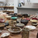 A mix of small ceramic pots sits on a wooden table. They are all around palm size with brown, blue, grey, white and purple glazes and different textures. Some have been thrown on the wheel and others are handbuilt.