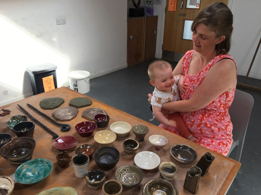 A white woman, Becky, with shoulder-length blonde hair and wearing a red and pink spotty boiler suit sits at a table in the SSW studio holding baby Olwen who is grinning. On the table are lots of ceramic bowls in different colours and shapes laid out.